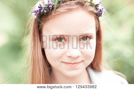 Smiling teenage girl 10-12 year old posing outdoors. Looking at camera. Wearing flower hairband.