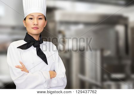 Portrait of confident female cook in kitchen against pots standing on hotplate