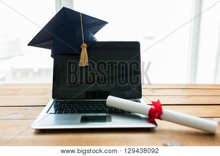 education, graduation, technology and e-learning concept - close up of laptop computer with mortarboard and diploma scroll on wooden table