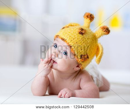 funny baby weared giraffe hat lying on bed in nursery