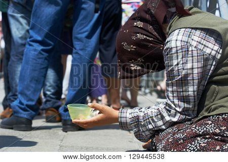 beggar woman begging for money in the street