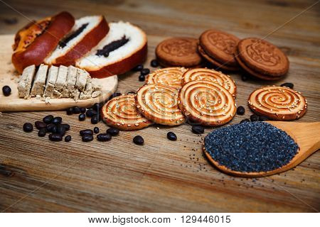 There are Pieces of Roll with Poppyseed,Cookies and Halavah,Chocolate Peas.Tasty Sweet Food on the Wooden Background
