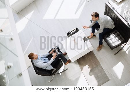 Business meeting in lobby by two businessmen