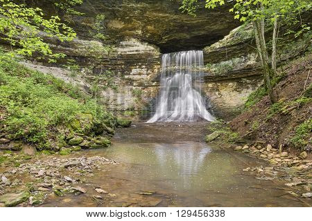 Porter Falls a waterfall in rural Indiana flows from a large cave and over a steep cliff.