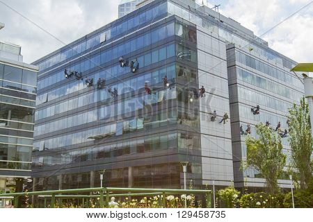 December 4 2015 - Buenos Aires Argentina : Window washers hanging from ropes outside modern glass building in Buenos Aires Argentina.