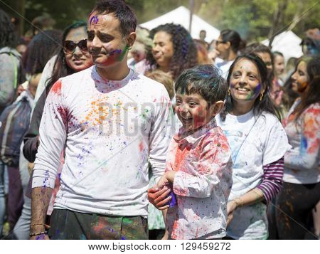 NEW YORK - APR 30 2016: A family celebrates Holi Hai Festival of Colors with colorful powder on their faces in Dag Hammerskjold Plaza hosted by NYC Bhangra in New York on April 30, 2016.