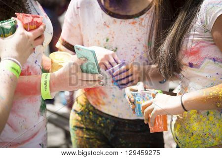 NEW YORK - APR 30 2016: Spectators celebrating with colorful powder on their clothes look at pictures on a cellphone at Holi Hai Festival of Colors hosted by NYC Bhangra in New York April 30 2016.