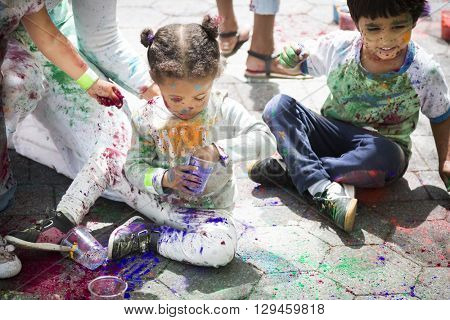 NEW YORK - APR 30 2016: Kids sit on the sidewalk playing with colorful powder on their faces to celebrate Holi Hai Festival of Colors hosted by NYC Bhangra in New York on April 30, 2016.