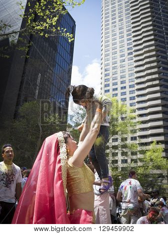 NEW YORK - APR 30 2016: A female member from NYC Bhangra dances with a little girl in the crowd at the Holi Hai Festival of Colors in Dag Hammerskjold Plaza in New York April 30, 2016.