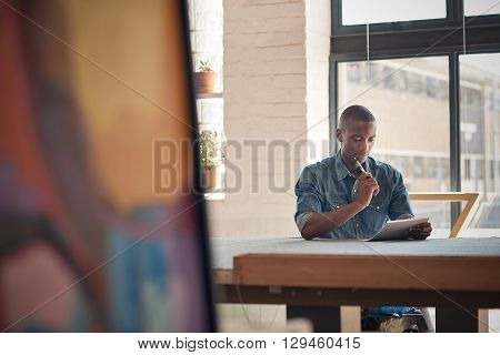 Handsome young Afican entrepreneur sitting at a work table with paper and pen, pausing to think while making plans for his future