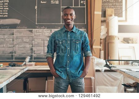 Portrait of a handsome contemporary young designer of African descent, smiling at the camera while standing in his studio workshop space with his hands in pockets and a confident expression