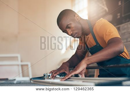 Young craftsman of African descent concentrating carefully while using a cutting tool with skill and expertise in a beautifully lit picture framing workshop