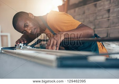 Low angle shot of a focused young artisan of African descent, working in a picture framing workshop, using a cutting tool with skill and expertise