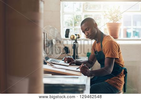 Handsome small business owner of African descent, sitting at his desk in his beautifully lit studio, working with his laptop and paperwork