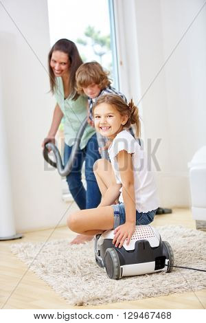 Mother and children having fun doing housecleaning with a vacuum cleaner