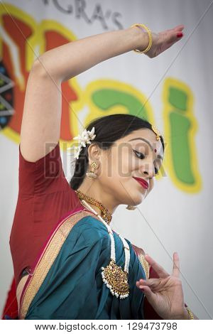NEW YORK - APR 30 2016: A female dancer from NYC Bhangra uses the katakamukha mudra, a hand gesture, while performing on stage at the Holi Hai Festival of Colors in New York on April 30 2016.