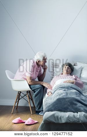 Senior man sitting on a chair beside his sick wife