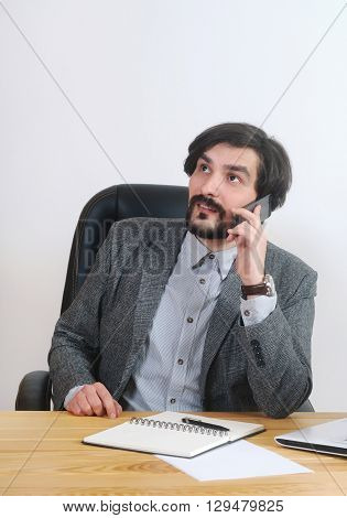An Attractive Businessman Speaking On His Mobile At His Desk In The Office