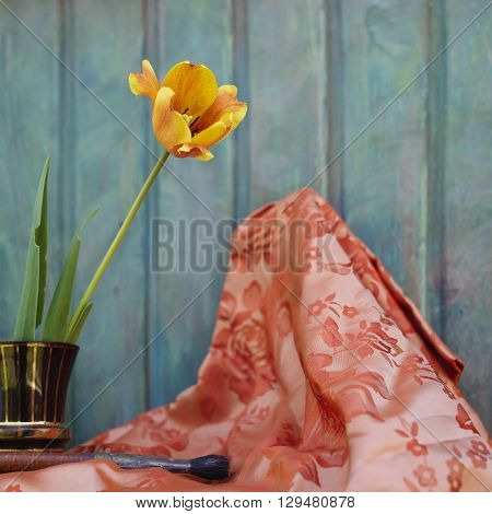 Preparation for a painting lesson on a Plein Air a beautiful tulip in a purple vase next to the paint brush. Outdoor cropped shot