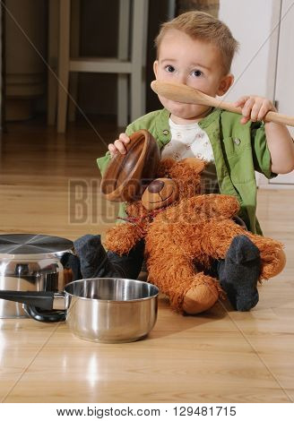 Cute Littel Boy Sitting On The Kitchen Floor Playing With Pots