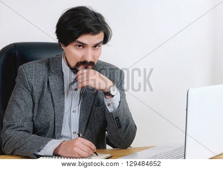 Portrait Of Attractive Serious Businessman Working At His Desk In The Office