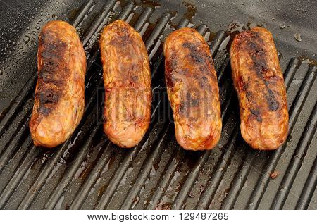 Freshly cooked pork sausages in a non stick griddle frying pan
