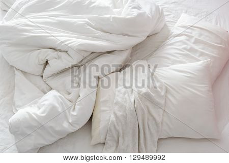 Top view of an unmade bed in a bedroom with crumpled bed sheet a blanket a white shower towel and two pillows after waking up in the morning. Not having bedclothes neatly arranged for sleep in.