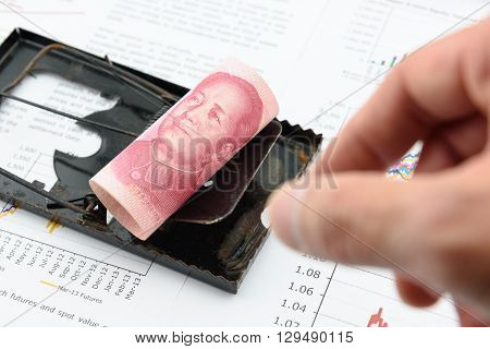 Rolled up scroll of CNY Chinese 100 yuan bill with portrait / image of Mao Zedong on a black rat trap. Using money as a bait to lure someone for illegal / dishonest things. China financial concept.