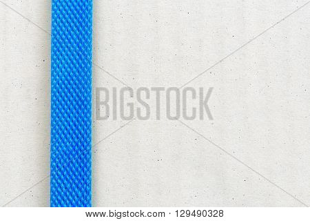 Light brown cardboard box / parcel fastened with blue plastic / nylon strap before shipping to several area i.e. domestic or overseas. Abstract texture background for your creative design / ideas.
