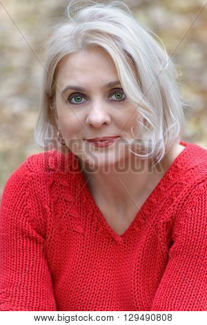 Portrait of a green-eyed blonde in the red sweater