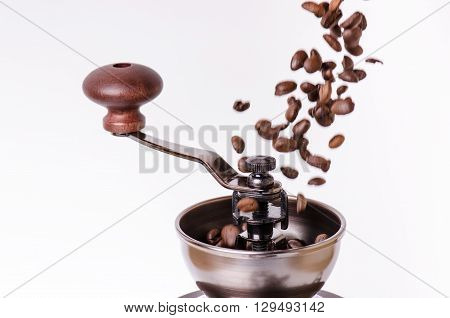 Manual coffee grinder with coffee beans. Isolated. White background. Modern style. Roasted coffee beans. Levitation coffee beans.