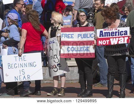 Asheville, North Carolina, USA - February 28, 2016: Crowd of Bernie Sanders supporters of all ages stand on a street corner holding signs and interacting with cars and passersby during a political rally on February 28 2016 in downtown Asheville, NC