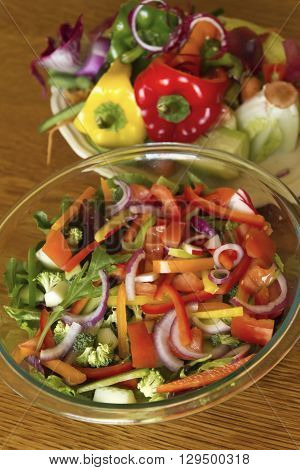 A large colorful raw summer vegetable salad in a glass bowl next to a very large plate overflowing with the wasted peelings and discarded vegetable scraps from the making of it