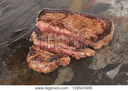 Sirloin steak slices against grey slate backround