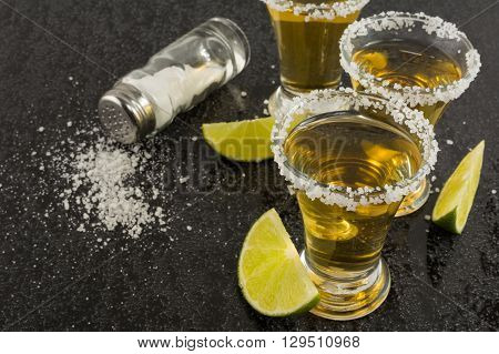 Gold tequila shots with lime on black background. Gold Mexican tequila. Tequila shot. Tequila.