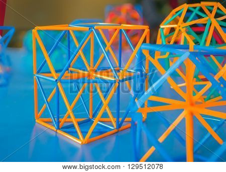 Coloured three-dimensional model of geometric solids on the blue table defocused.