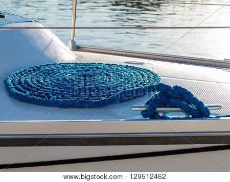 Blue Rope Coiled On Dock And Tied To Metal Cleat.
