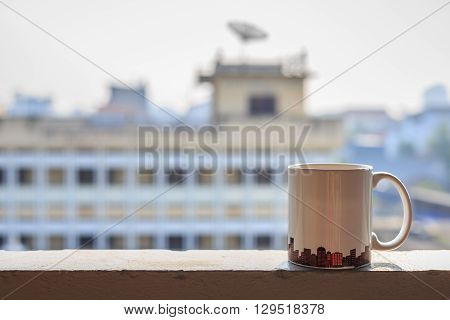 Close up coffee cup on balcony and blurred view of building