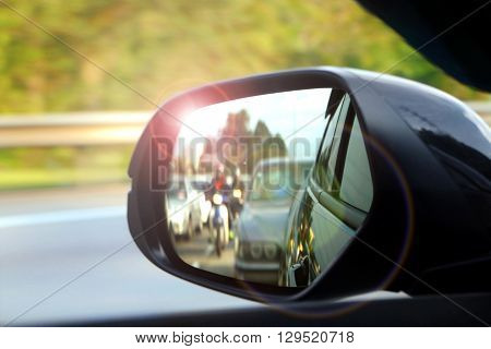 Car side mirror view with sunlight glare