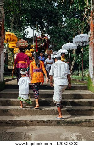 UBUD INDONESIA - MARCH 02: Balinese family in traditional clothes going to the temple during Balinese New Year or Nyepi Day celebrations on March 02 2016 in Ubud Bali.