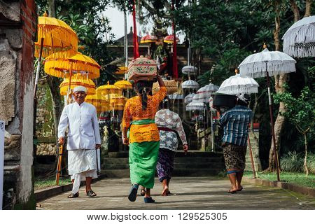 UBUD INDONESIA - MARCH 02: Balinese people in traditional clothes going to the temple with offerings during Balinese New Year or Nyepi Day celebrations on March 02 2016 in Ubud Bali.