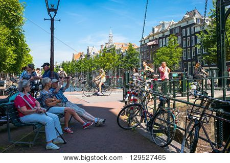 Amsterdam Holland - July 22 2014: Red Light district. local people and tourists relaxing near a traditional drawbridge