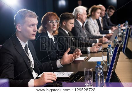 Politician debating at a desk with microphones