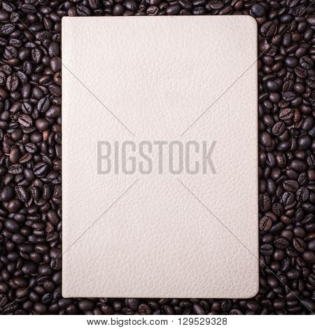 Coffee Beans And Note Book On Wooden Background