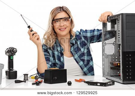 Female PC technician posing next to a disassembled desktop computer isolated on white background