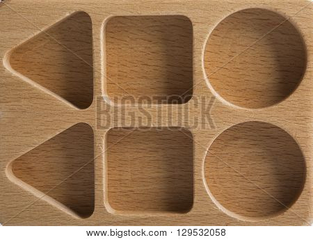 Baby sorter with geometric figures from wood on a white isolated background