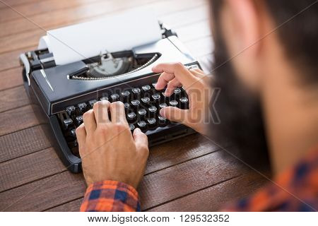 A man is typing on a type writer on his desk