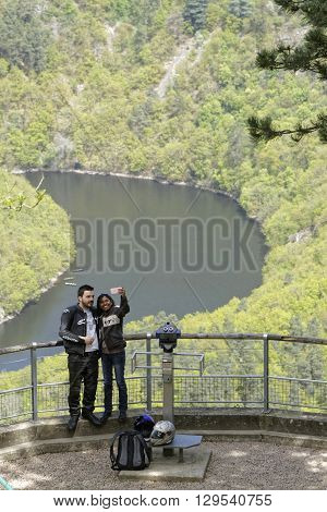 QUEUILLE FRANCE May 6 2016 : Young couple does selfie in Meandres de Queuille. Left tributary of the river Allier the Sioule river has cut a deep gorge in the landscape.
