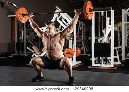 Muscular man at a crossfit gym lifting a barbell.