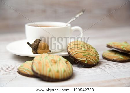 A cup with a drink and chocolate chip cookies on the table